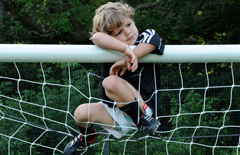 boy hanging on soccer goal